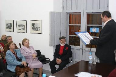 """En la imagen, José Luis dicta una conferencia sobre el tema """" Triana y el Flamenco""""  en el Salón de actos del Centro Cívico """"Casa de las Columnas de Triana"""". Sentado en primer término, con camisa y pañuelo rojos, """"El Herejía"""""""